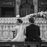 Boda Alicia y Ariel - Novios desde atrás sentados en iglesia - Santiago Stankovic Fotógrafo